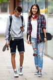 Teenage friends carrying skateboards in the city Royalty Free Stock Images