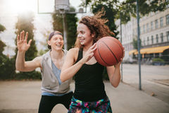 Teenage friends enjoying a game of streetball. Young girl playing basketball with boy blocking. Teenage friends enjoying a game of streetball on outdoor court Royalty Free Stock Photography