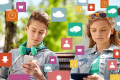Teenage friends with gadgets outdoors. Technology, internet and people concept - teenage boy with smartphone and headphones and girl with tablet pc computer Stock Images