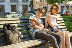 Teenage friends girl and boy sitting on bench in city, smiling, talking, looking in phone. Friendship and people concept stock photos
