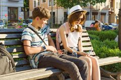Teenage friends girl and boy sitting on bench in city, smiling, talking, looking in phone. Friendship and people concept stock photo