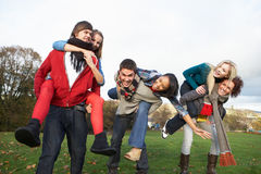 Teenage Friends Having Piggyback Rides. Group Of Teenage Friends Having Piggyback Rides In Autumn Landscape Stock Photography