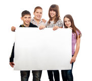 Teenage friends holding giant empty paper Royalty Free Stock Photos