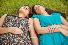 Teenage friends napping. Cute female best friends relaxing and listening to music at a park Royalty Free Stock Photography