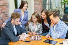 Teenage friends playing a chess game and thinking on a cafe background. Chess play concept. Stock Photo