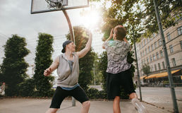 Teenage friends playing a game of basketball. Two young men playing basketball against each other. Teenage friends playing a game of basketball on an outdoor Stock Photo