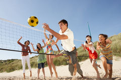 Teenage Friends Playing Volleyball On Beach. Group Of Teenage Friends Playing Volleyball On Beach royalty free stock photography