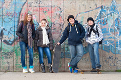 Teenage friends with school bags and skateboards. Happy teenage friends with school bags and skateboards standing in front of the graffiti wall royalty free stock images
