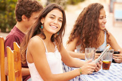 Teenage Friends Sitting At Caf� Using Digital Devices Royalty Free Stock Image
