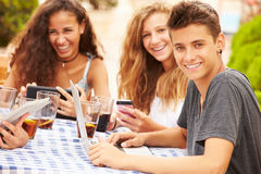 Teenage Friends Sitting At Caf� Using Digital Devices Royalty Free Stock Photography