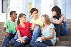 Teenage Friends Sitting On College Steps Outside. Group Of Teenage Friends Sitting On College Steps Outside Stock Image