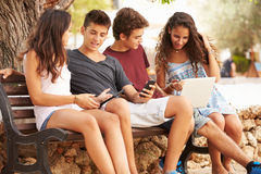 Teenage Friends Sitting In Park Using Digital Devices Stock Image