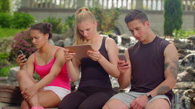 Teenage friends using digital devices outdoor. Mobile communication technology. Connection concept. Young people hanging in tablet and smartphones. Social stock video footage