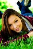 Teenage Girl. Beautiful african american teenage girl laying in the grass royalty free stock photo