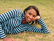 Teenage Girl. Jasmine is laying on the grass outside enjoying a nice fall day Stock Photo