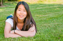 Teenage Girl. Beautiful young smiling Asian American girl with long hair lying on stomach on lawn with arms crossed. Horizontal. Copy space Royalty Free Stock Images