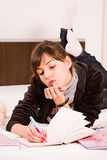 Teenage girl. Standing in her bed with her diary, holding her finger at mouth Royalty Free Stock Photo