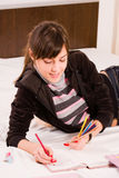 Teenage girl. Writing in her diary, with colored pencils in her hand Royalty Free Stock Images
