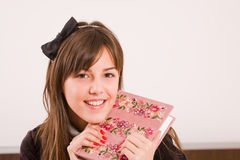 Teenage girl. Funny teenage girl smiling, holding her diary or notebook Stock Image