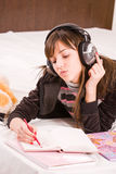 Teenage girl. Writing in her diary an listening to music in professional earphones Stock Photos