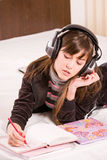 Teenage girl. Writing in her diary an listening to music in professional earphones Stock Image