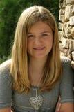 Teenage girl. Smiling showing braces wearing a grey shirt Stock Image