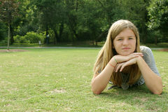 Teenage girl. Wearing a gray shirt laying in the grass Stock Photos