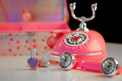 Teenage Girl Accessories. Princess telephone, nail polish and jewelry box in girl's room Royalty Free Stock Photo