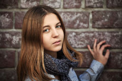 Sad fashion teen girl against a brick wall Stock Photo