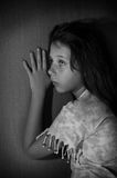 Teenage girl against wall. Teenage girl leaning against dark wall black and white royalty free stock photography