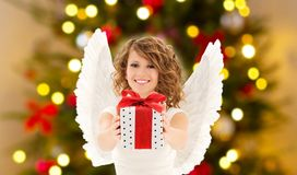 Teenage girl with angel wings and christmas gift. Holidays concept - happy teenage girl with angel wings holding gift box over christmas thee lights background royalty free stock photos
