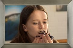 Teenage girl applies black lipstick Royalty Free Stock Images