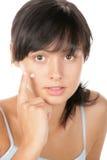 Teenage girl applying cream Stock Images