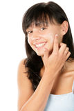 Teenage girl applying facial cream Stock Photos