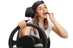 Teenage girl applying lipstick and driving Stock Images
