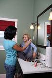 Teenage girl applying makeup to girl Royalty Free Stock Photography