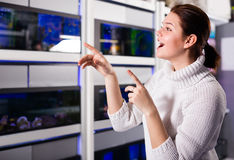 Teenage girl in aquarium shop is looking at different colored fi Royalty Free Stock Image