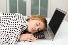 A teenage girl asleep at a computer Stock Image