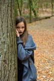 Teenage girl in autumn forest. Young girl is leaning against a tree trunk in the autumn forest royalty free stock photos
