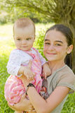 Teenage girl with a baby girl. A teenage girl with a baby in arms stock photography