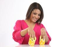 Teenage girl  with baby shoes Stock Image