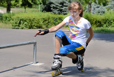 Teenage girl balancing on her rollerblades Stock Images