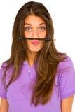 Teenage girl balancing pencil on her lip Stock Image