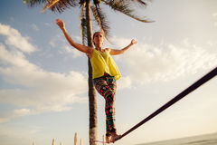 Teenage girl  balancing on slackline with sky view Royalty Free Stock Photos