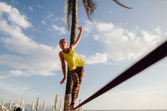 Teenage girl  balancing on slackline with sky view Stock Images