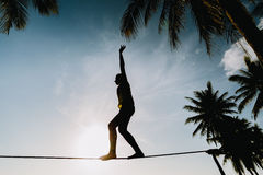 Teenage girl balancing on slackline with sky view. On the beach silhouette royalty free stock photos