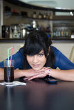 Teenage girl in bar Stock Image