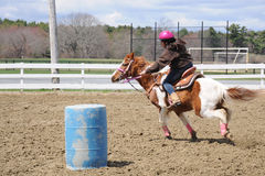 Teenage girl barrel racing. A young teenage girl turns around a barrel and races to the finish line Royalty Free Stock Image