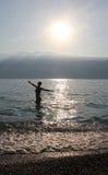 Teenage girl, bathing in a lake, morning sun. Teenage girl silhouette, bathing in garda lake, bright morning sun Royalty Free Stock Image