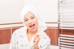 Teenage girl in bathroom with toothbrush. Morning and evening de Stock Image
